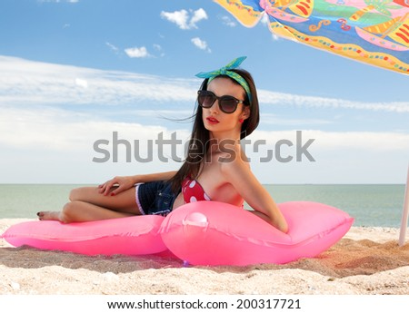 Fashionable woman in stylish swimsuit on beach - stock photo