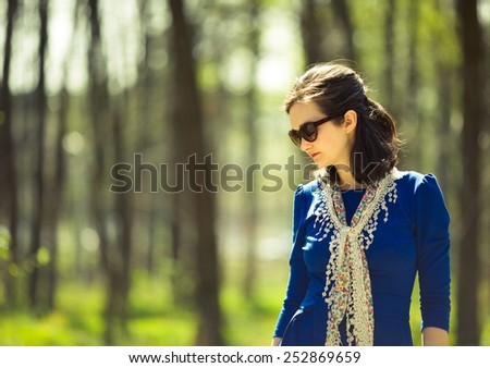 Fashionable woman in the park. Looking down. Natural light. Summer. Sun glasses. Colorful neckerchief. - stock photo