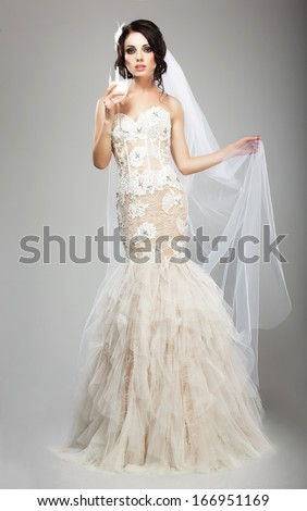 Fashionable Woman in White Dress holding Wineglass of Champagne - stock photo