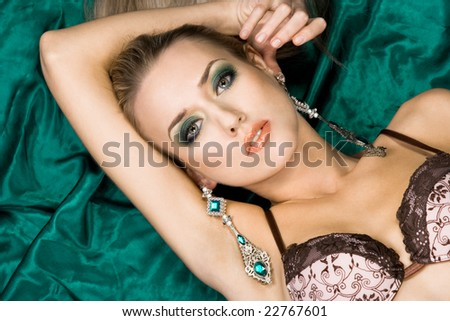 fashionable woman lying on green background