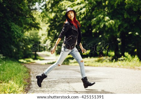 Fashionable woman posing in the woods on the road