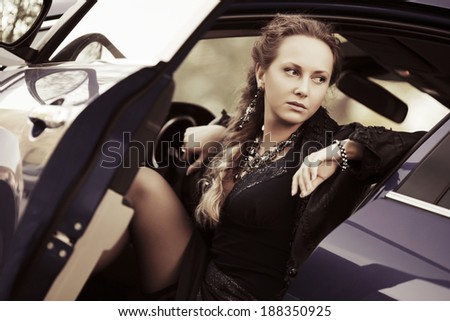 Fashionable woman sitting in a car  - stock photo