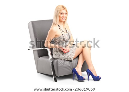 Fashionable woman sitting in a modern armchair isolated on white background - stock photo