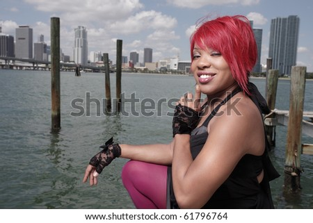 Fashionable woman smiling with downtown in the background - stock photo