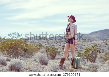 fashionable woman traveler walking with suitcase and luggage in desert
