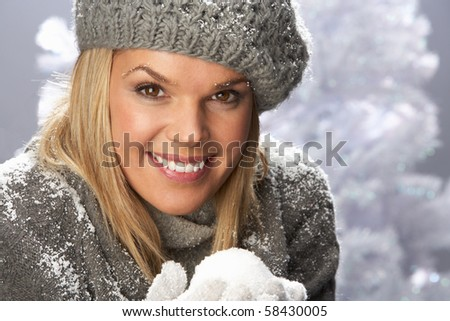 Fashionable Woman Wearing Cap And Knitwear Holding Snowball In Studio In Front Of Christmas Tree - stock photo