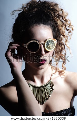 Fashionable woman with curly hair in eyeglasses made from dried lemon slices