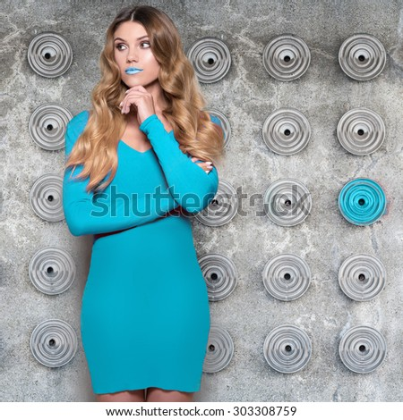 fashionable woman with long brown hair wearing blue dress standing against the wall - stock photo