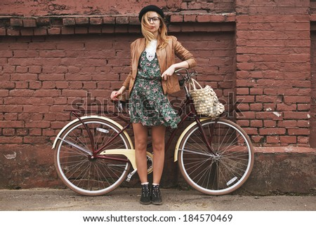 fashionable woman with vintage bike on brick wall background - stock photo
