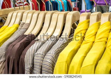 Fashionable women clothing on hangers in shop - stock photo