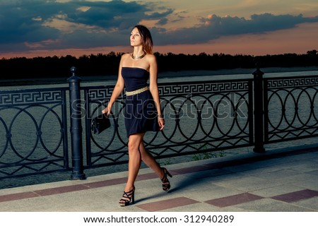 Fashionable women is walking in evening time with her trendy clutch covered with rivets in hands. We can see colorful sunset sky over her. Toned in warm colors. Outdoors shot, lifestyle. - stock photo