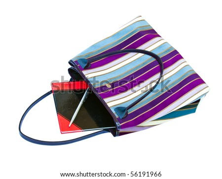 Fashionable women's handbag with a notebook and pen isolated on white background.