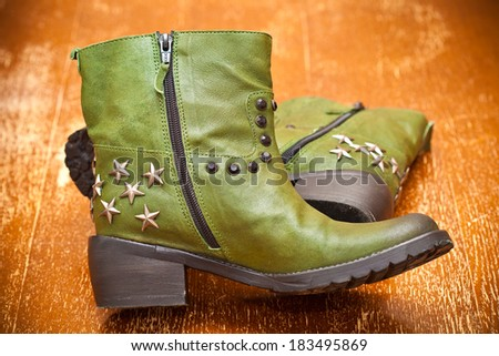 Fashionable women's leather shoes green. Cowboy boots with stars - stock photo