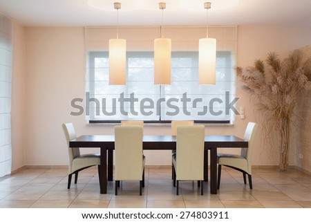 Fashionable wooden table in bright dinning room - stock photo