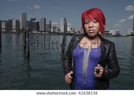 Fashionable young African American female posing with downtown in the background - stock photo