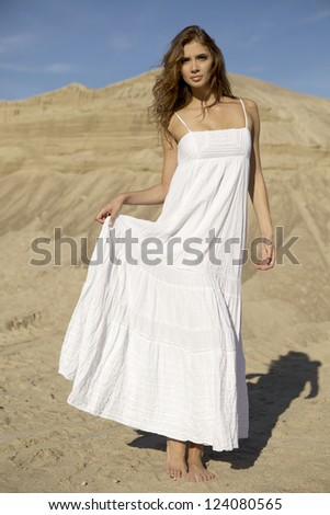 Fashionable young attractive and sensuality brunette woman in white dress dancing on the desert - stock photo