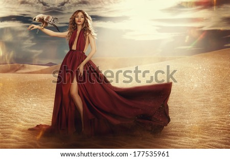 fashionable young attractive and sensuality woman in the desert in long red dress with eagle sitting on her hand. - stock photo