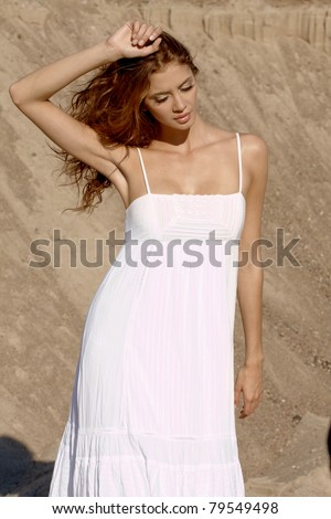 fashionable young attractive woman in the desert over sand background wearing white dress - stock photo