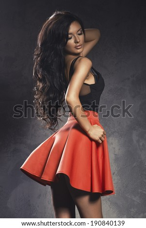 Fashionable young brunette sensual woman posing in elegant red dress. Long curly hair.  - stock photo