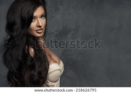 Fashionable young brunette sensual woman posing. Long curly hair.  - stock photo