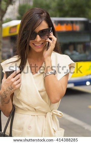 Fashionable young brunette wearing short white dress and sunglasses laughs into phone on city street near bus - stock photo