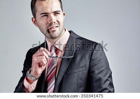 Fashionable young businessman holding his glasses to his lips isolated over grey - stock photo