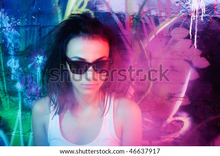 Fashionable young clubber woman against graffiti wall.