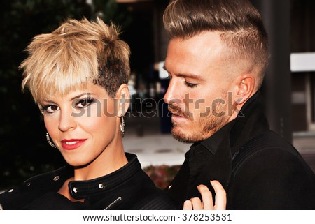 Fashionable young couple dress in black with trendy hairstyle. Urban fashion photography. Vertical image.