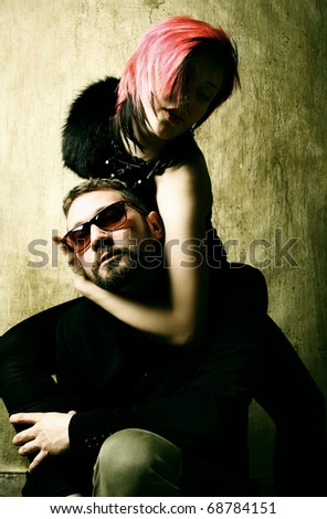 Fashionable young couple in love isolated on grunge background - stock photo
