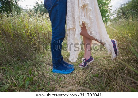 Fashionable young couple in sneakers on nature, legs, lifestyle-concept - stock photo