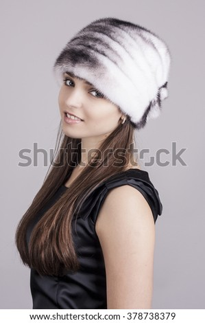 Fashionable young girl in a hat. Hat made of natural mink.