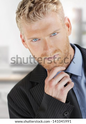 Fashionable young handsome business man with nice blue eyes in suit - stock photo
