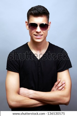 Fashionable young happy guy in sunglasses over grey background - stock photo