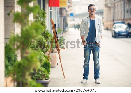 Fashionable young man standing on the street with hands in his pockets - stock photo