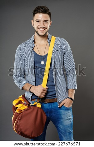 Fashionable young man with bag on gray background - stock photo