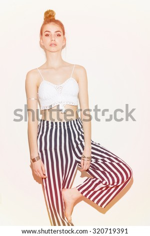Fashionable young model woman posing. Trendy bare feet boho teenage girl with bun hairstyle wearing white crochet crop top, striped pants posing against white background, vertical, pastel pink filter - stock photo