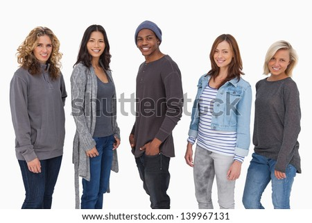 Fashionable young people in a line smiling on white background - stock photo