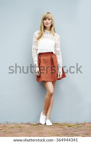 Fashionable young woman against wall, portrait - stock photo