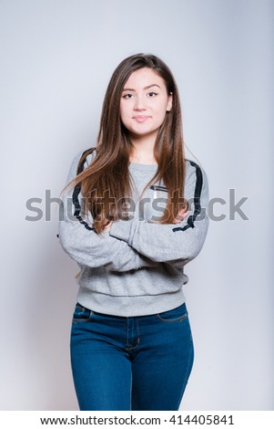 Fashionable young woman folded her arms crosswise, close-up isolated on a gray background - stock photo