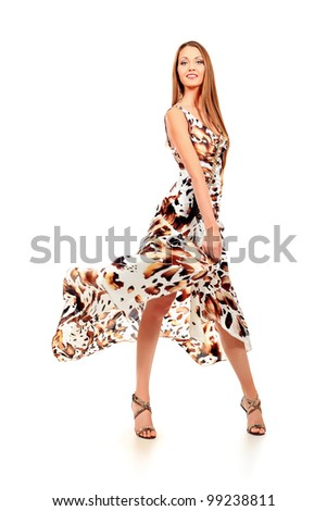 Fashionable young woman in beautiful dress posing at studio. Isolated over white. - stock photo