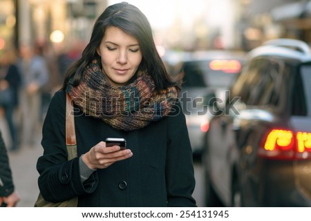 Fashionable Young Woman in Black Coat and Colorful Scarf Busy with her Mobile Phone While Walking a City Street - stock photo