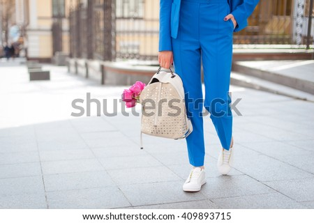 Fashionable young woman in blue suit and white sneakers on the city streets. Fashion. Backpack. Shawl.