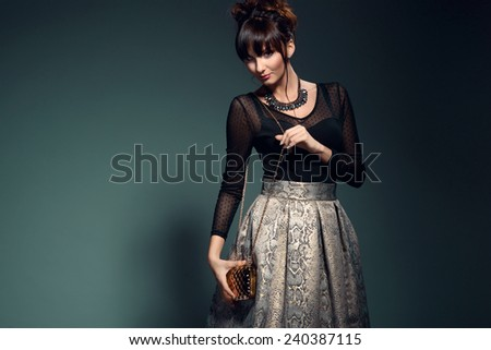 Fashionable young woman in elegant golden skirt and black transparent top, holding evening handbag. Glamour style  - stock photo