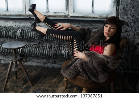 Fashionable young woman in fur coat posing in a vintage interior, horizontal shot - stock photo