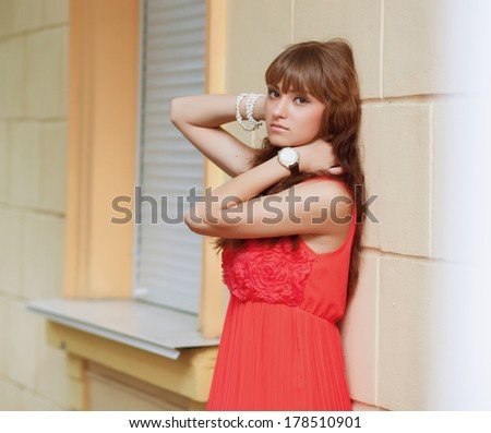 fashionable young woman in summer dress posing against old stone wall. soft sunny colors.
