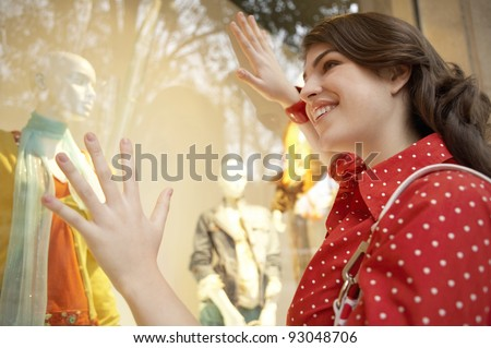 Fashionable young woman looking at clothes shop window. - stock photo