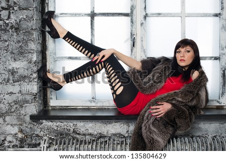 Fashionable young woman posing on a window sill, studio shot - stock photo