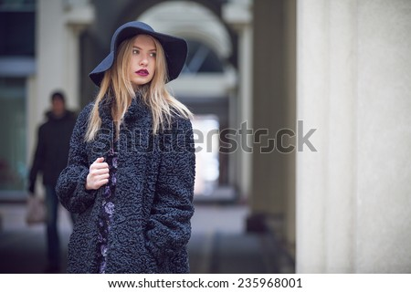 Fashionable young woman posing outside in a city street. Winter Fashion - stock photo