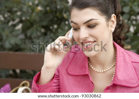 Fashionable young woman sitting down on a bench, using a cell phone. - stock photo