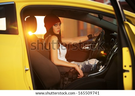 Fashionable young woman sitting in a car - stock photo